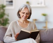 senior woman reading a book on her couch at home