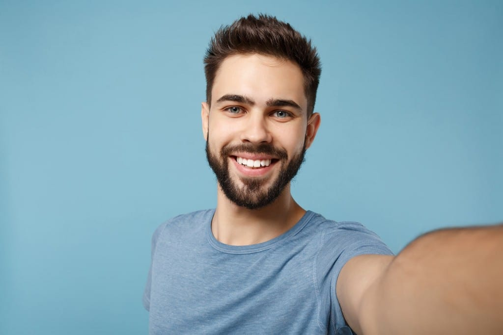 man showing off his white smile to the camera while taking a selfie