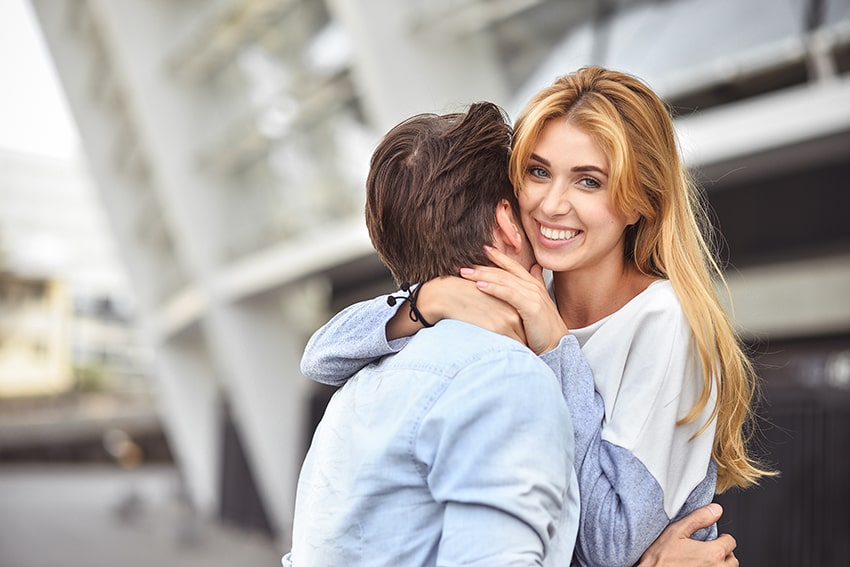 Happy young couple hugging and laughing outdoors. Let your new smile impact your relationship but celebrating the next six months.