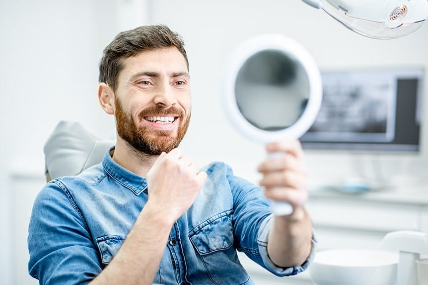 Male checks out this new smile with a hand held mirror