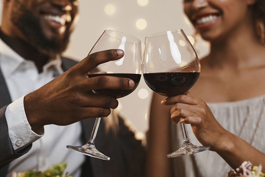 couple celebrating with glasses of red wine